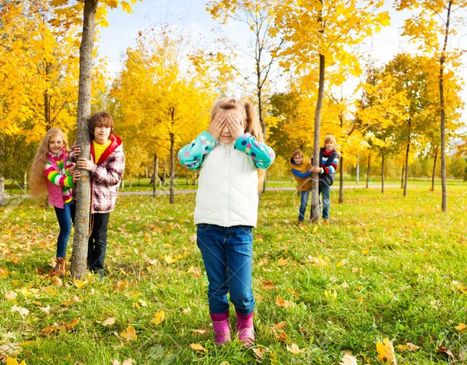 Children playing hide and seek in a park in the fall.