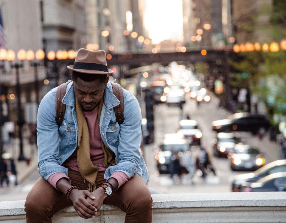Man sitting on wall downtown looking sad