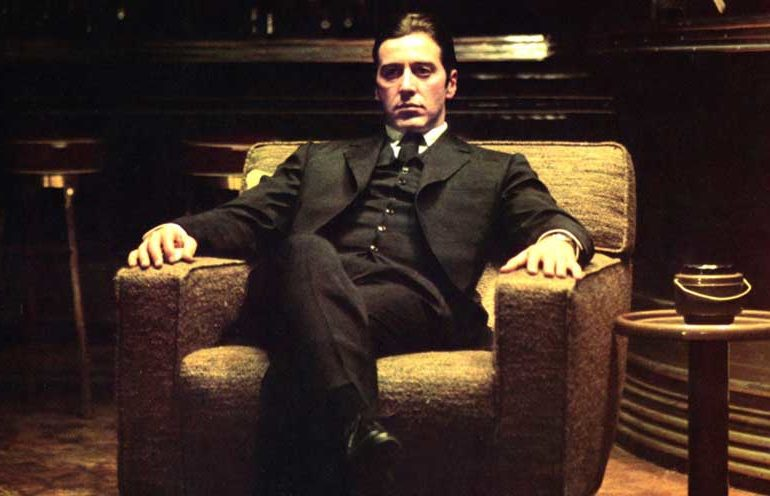 Al Pacino in character in the movie The Godfather, sitting in an upholstered chair staring outward, dispassionate and disconnected